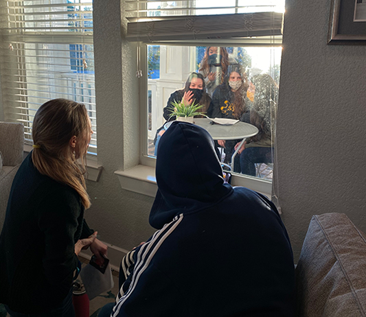 SAGU students speaking with Daymark residents through the window meeting